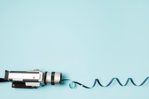 青色の背景にビデオカメラから渦巻き模様のフィルムストライプ
