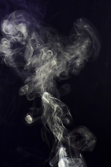 Swirling of white smoke on black background