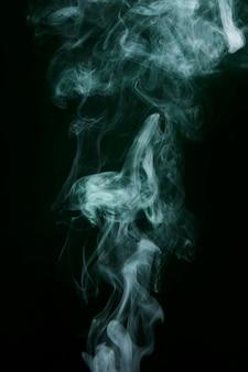 Swirling white smoke on black background