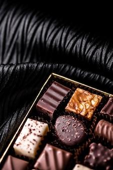 ギフトボックスにスイスのチョコレートホリデープレゼントとプレミアム菓子ブランドとしてスイスの甘いデザート食品のショコラティエにダークチョコレートとミルクオーガニックチョコレートで作られたさまざまな豪華なプラリネ
