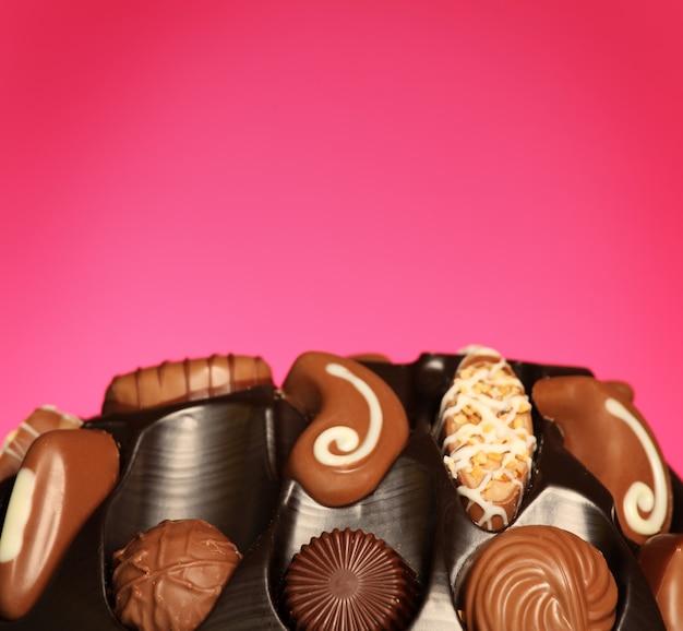 Швейцарские шоколадные конфеты на розовом фоне