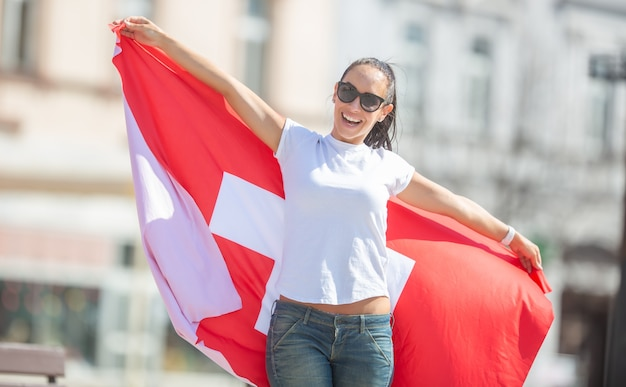 Швейцарская фанатка держит флаг на улице, улыбаясь в солнечный день.