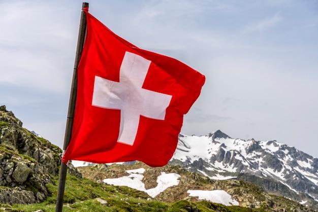 雪に覆われたアルプスの山々のスイス国旗-セレクティブフォーカス