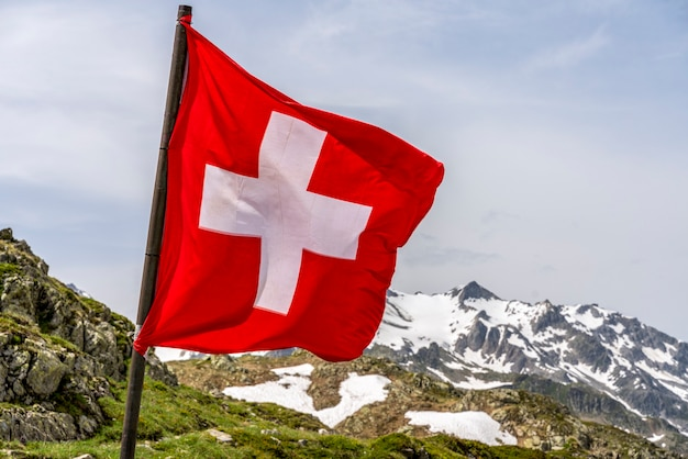 Swiss flag in the snowy alps mountains - selective focus