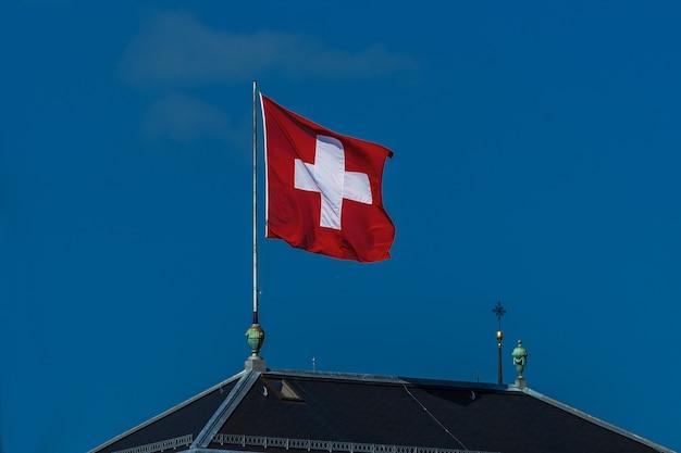 푸른 하늘을 배경으로 바람에 흔들리는 스위스 국기