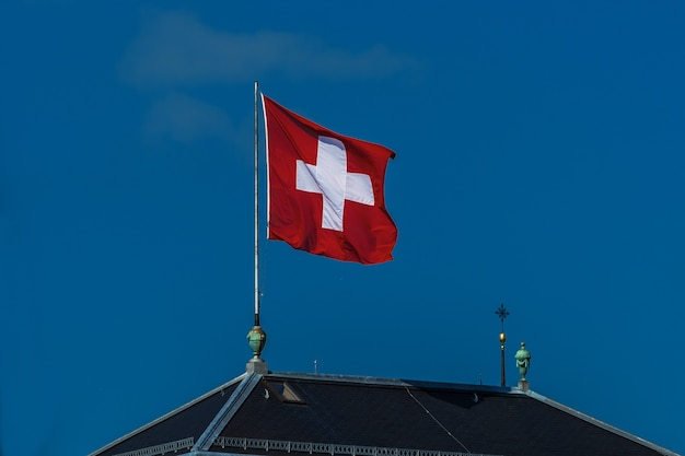 Swiss flag waving in the wind against a blue sky