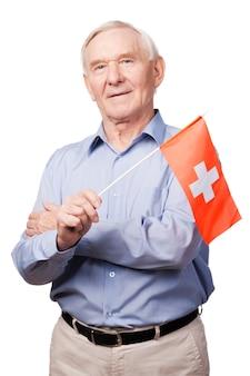스위스 우정. 스위스 국기를 들고 흰색 배경에 서서 카메라를 보며 웃고 있는 쾌활한 노인