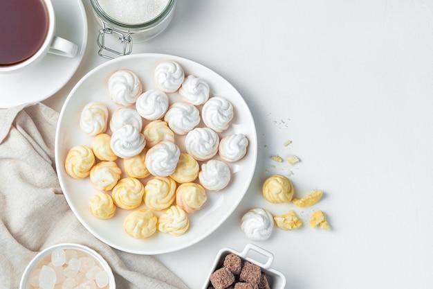 Швейцарские безе в тарелке на светлом фоне. концепция десертов.