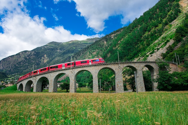 Swiss mountain train bernina express cross the bridge in the cir