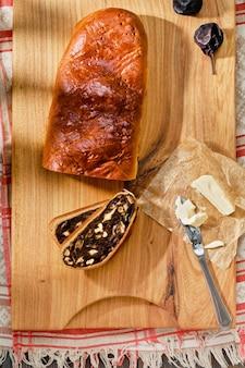 Швейцарский грушевый хлеб - birnbrot. местная выпечка с начинкой из сушеных груш, орехов и фруктов. вид сверху свежеиспеченного грушевого хлеба, нарезанного ломтиками, рядом с маслом. праздничный завтрак