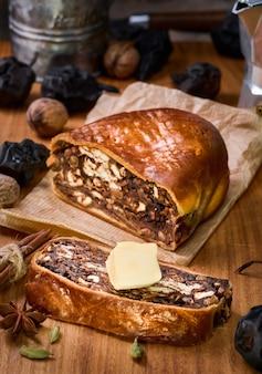 Швейцарский грушевый хлеб или birnbrot - местная выпечка с начинкой из сушеных груш и фруктов. выборочный фокус. нарезанные дольками маффина, рядом сливочное масло. вертикальная фотография
