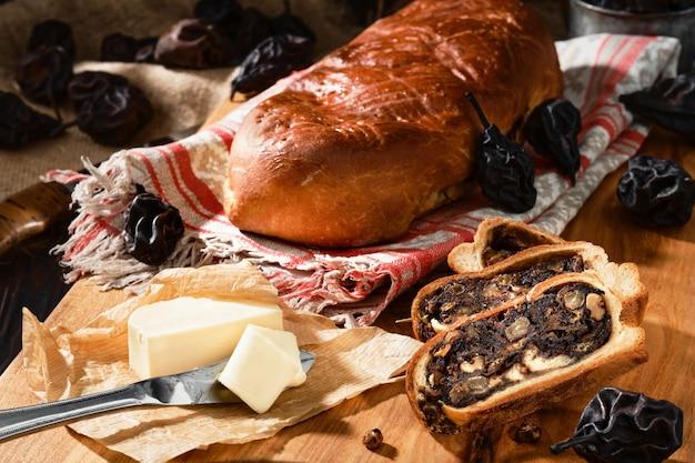 Швейцарский грушевый хлеб или birnbrot - это традиционный бисквит с начинкой из сушеных груш и фруктов. нарезанные дольками маффина, рядом сливочное масло. горизонтальная фотография