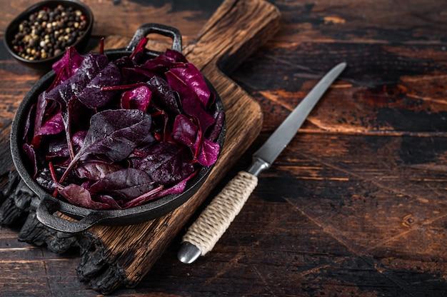 Швейцарский красный мангольд или листья салата мангольд на сковороде. темный деревянный стол. вид сверху. скопируйте пространство.