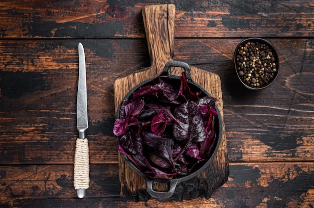 Швейцарский красный мангольд или листья салата мангольд на сковороде. темный деревянный стол. вид сверху.