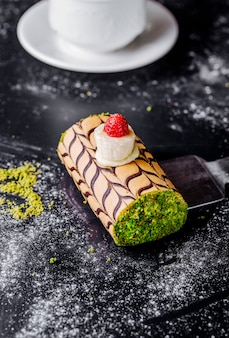 Swiss roll cake with pistachio minced and vanilla cream with cherry.