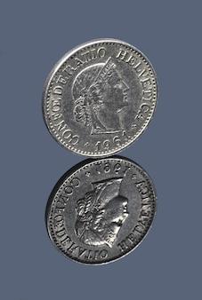 Swiss ten centimes coin on dark mirror surface