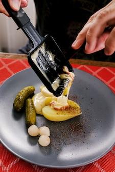 Швейцарское традиционное блюдо, называемое раклет, включает жареный картофель, плавленый сыр и соленые огурцы, которые едят на рождество и зимой.