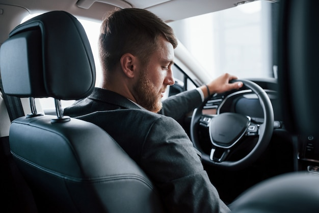 Переключение передач. современный бизнесмен пробует свою новую машину в автомобильном салоне