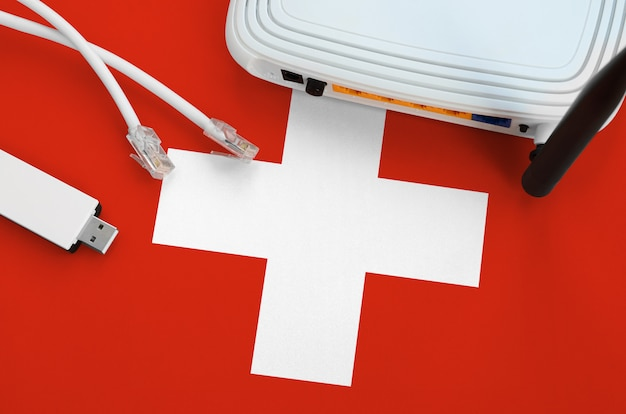 Switzerland flag depicted on table with internet rj45 cable, wireless usb wifi adapter and router. internet connection concept