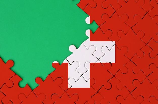 스위스 국기는 왼쪽에 무료 녹색 복사 공간이있는 완성 된 직소 퍼즐로 그려져 있습니다.