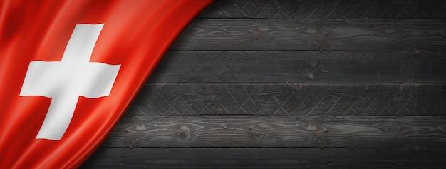 黒い木の壁にスイスの旗。水平方向のパノラマバナー。