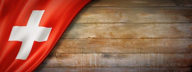 ヴィンテージの木製の壁にスイス国旗