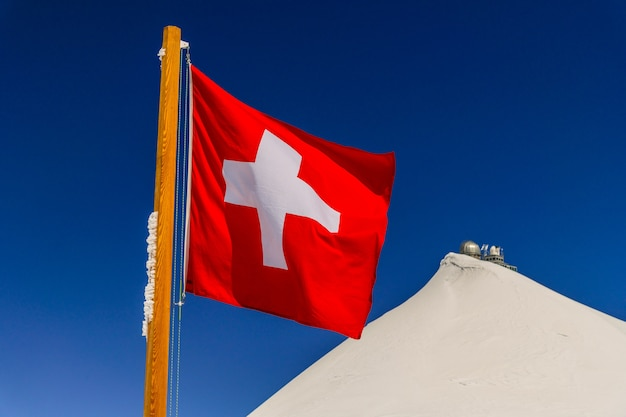 Switzerland flag and sphinx observatory  at top of jungfraujoch