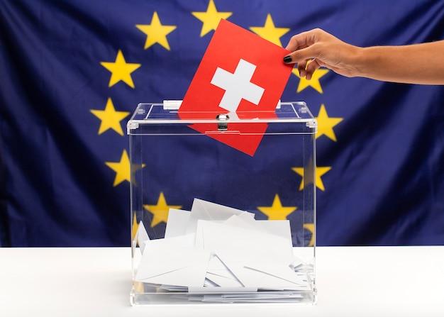 Бюллетень для голосования с флагом швейцарии на фоне европейского союза