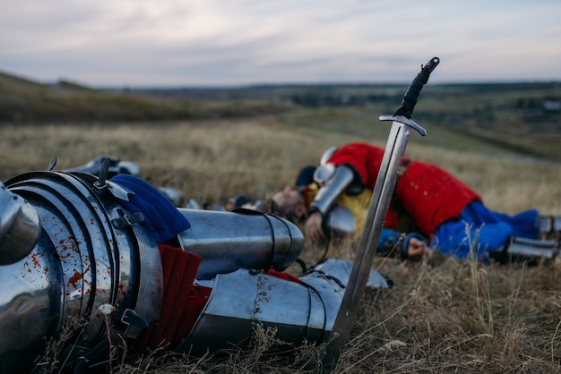 Меч застрял в земле и металлический рыцарский шлем