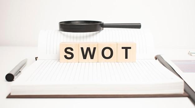 Swot 단어 개념입니다. 나무 큐브, 메모장, 펜 및 비즈니스 차트.