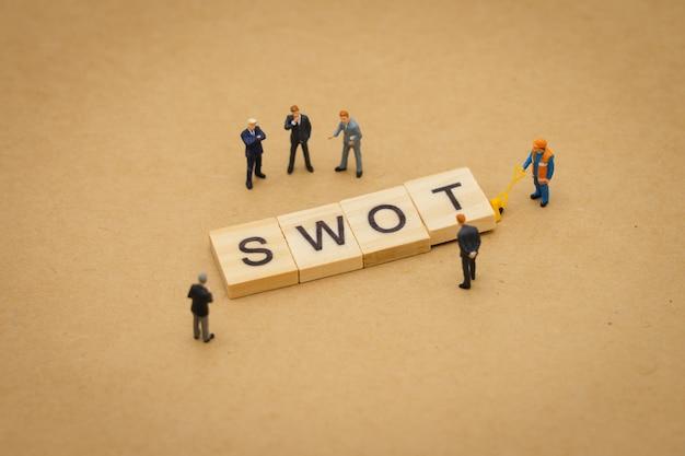 背景として使用する木製の単語swotと立っているミニチュアの人々ビジネスマン