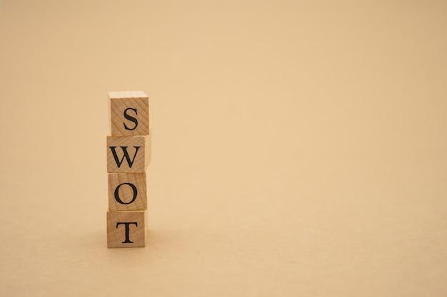 木のテーブル、戦略コンセプトに置かれた木製の単語swot