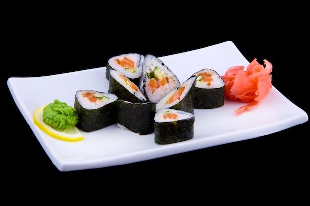 Syake ikuramaki-白い長方形のプレートに新鮮なサーモンとキュウリが入った巻き寿司。