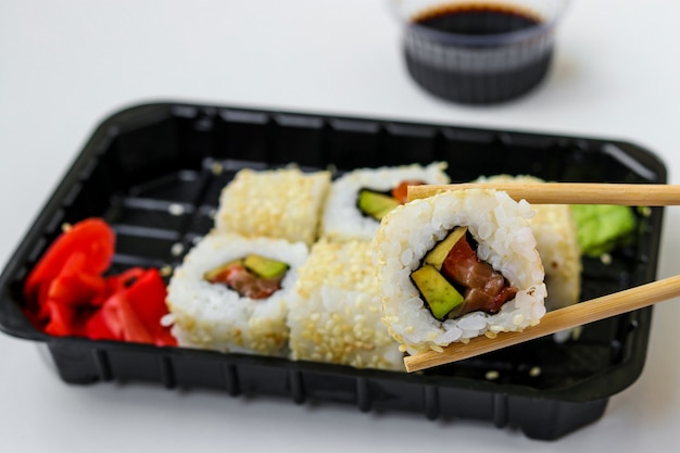 Syake rolls in a set of 6 pieces in a black box, with ginger, wasabi and soy sauce, fast food