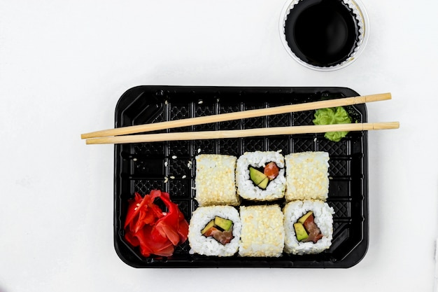 Syake rolls in a set of 6 pieces in a black box, with ginger, wasabi and soy sauce, horizontal orientation, top view