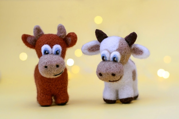 Symbol of 2021, a toy felt brown bulls on a festive light yellow background with bokeh, with a copy space
