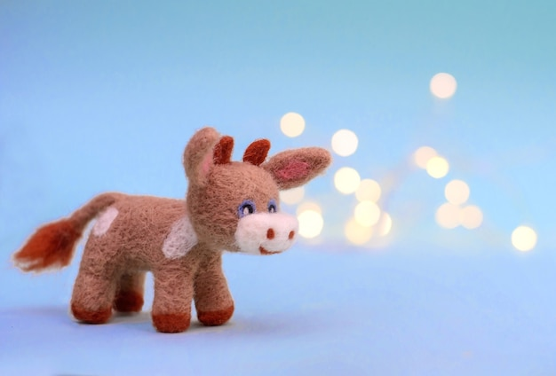Symbol of 2021, a toy felt bull or cow on a festive light blue background with bokeh, with a copy space