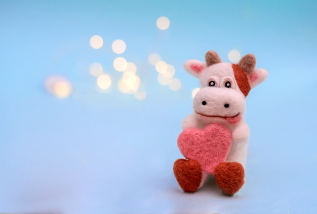 Symbol of 2021, a toy felt bull or cow with heart on a festive light blue background with bokeh, with a copy space