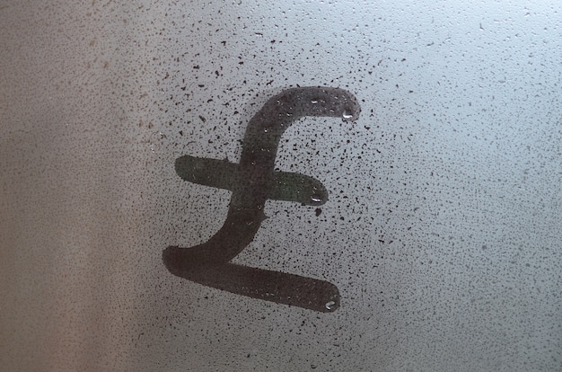 Symbol of english pounds is written with a finger on the surface of the misted glass