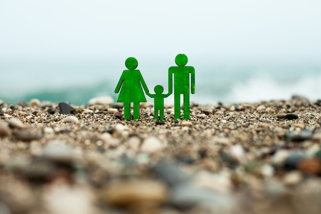 A symbol of the family against the background of the seashore figures of the father of mother and ch...