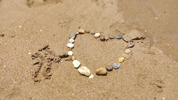 Symbol of the heart drawing stones on the sand. summer vacation