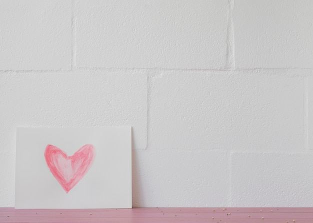Symbol of heart on white paper near wall
