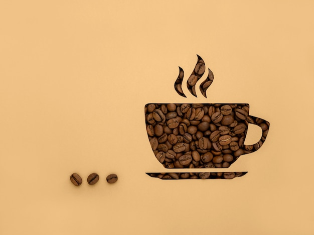 The symbol is a cup of black aromatic coffee beans. paper background, cut out, with copy of the space and space for text
