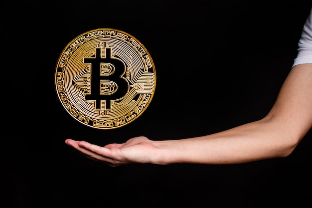 The symbol of the new popular cryptocurrency bitcoin with the image of hands