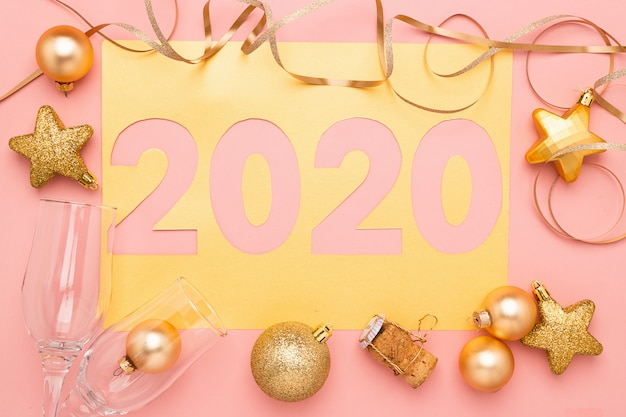 The symbol of the new year, numbers 2020 cut out of gold paper on pink paper background. new year or christmas concept.