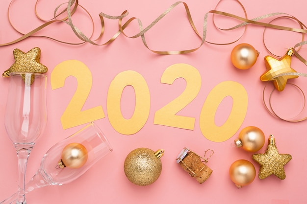The symbol of the new year, numbers 2020 cut out of gold paper on pink paper background.