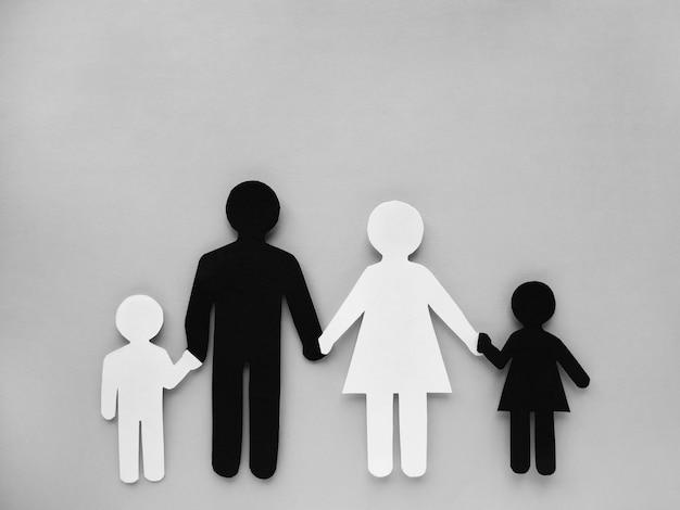 Символ человека и семьи вырезан из черно-белой бумаги. межрасовая семья.
