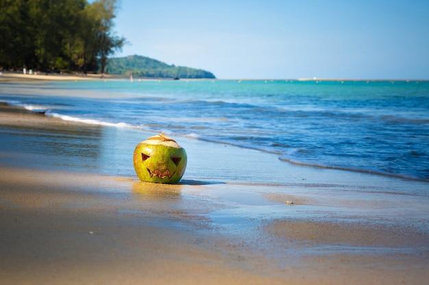 Символ хэллоуина кокос с лицом, вырезанным как фонарь джека свежий зеленый кокос на пляже