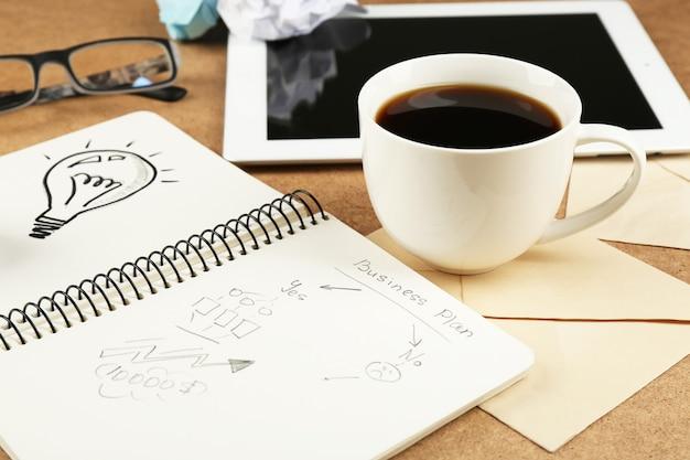 구겨진 종이, 태블릿 및 나무 책상에 커피 한잔과 함께 노트북에 전구로 아이디어의 상징