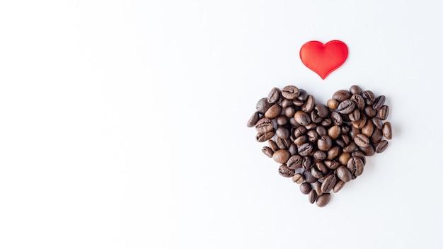 Символ любви к кофе. форма сердца из кофейных зерен и красного сердца на белом фоне